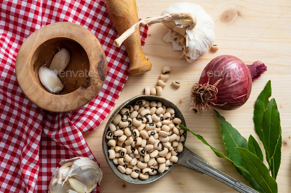 Black eyed beans, herbs and red tablecloth on wooden table, top view - Stock Photo - Images