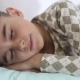 Mom Kisses Her Beloved Son While He Sleeps on the Bed and Smiles in His Sleep. - VideoHive Item for Sale