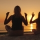Mom and Daughter Are Meditating By the Sea at Sunset - VideoHive Item for Sale