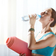Beautiful caucasian woman drinking water while holding yoga mat - PhotoDune Item for Sale
