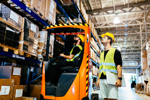 Warehouse workers working together with forklift loader - Stock Photo - Images