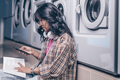 Young girl with a phone in laundry - PhotoDune Item for Sale