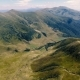 Aerial Shot of Rugged Carpathian Ranges with a Hilly Ravine in Summer - VideoHive Item for Sale