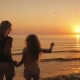 Mom and Daughter Are Walking on the Water Against the Backdrop of the Setting Sun - VideoHive Item for Sale