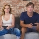 Emotional Man And Woman Play Joysticks in The Console, They Compete and Make Crazy Funny Faces - VideoHive Item for Sale