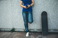 Skateboarder using mobile phone leaning against wall - PhotoDune Item for Sale