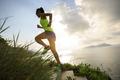 Woman runner running upstairs on seaside mountain trail - PhotoDune Item for Sale