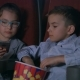Children Eating Popcorn in Cinema. Kids Using Mobile Phone at Cinema - VideoHive Item for Sale