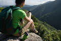 Hiking using mobile phone on cliff edge - PhotoDune Item for Sale
