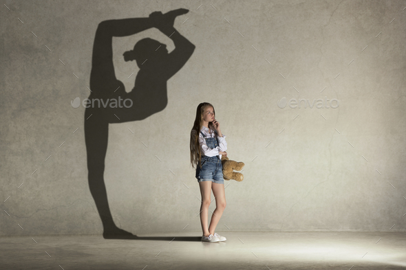 Baby girl dreaming about gymnast profession. Childhood concept. Stock Photo by master1305