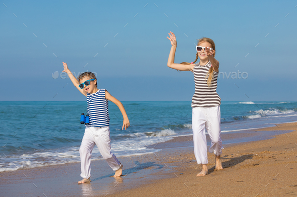 Two happy children playing on the beach at the day time - Stock Photo - Images