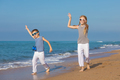 Two happy children playing on the beach at the day time - PhotoDune Item for Sale