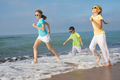 Three happy children running on the beach at the day time. - PhotoDune Item for Sale