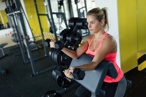 Beautiful girl doing exercise for biceps in gym - Stock Photo - Images