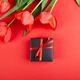 Black gift box with red ribbon near red tulip - PhotoDune Item for Sale