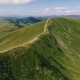 Aerial Shot of a Carpathian Ridge with a Country Road, Grassy Meadows in Summer - VideoHive Item for Sale