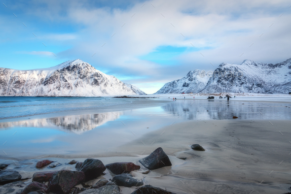 Snowy mountains and blue sky with clouds reflected in water - Stock Photo - Images
