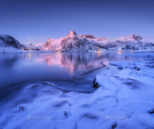 Frozen sea coast and beautiful snow covered mountains at dusk - Stock Photo - Images