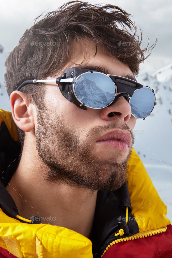 Portrait of mountaineer in winter clothes and ultraviolet protected sunglasses - Stock Photo - Images