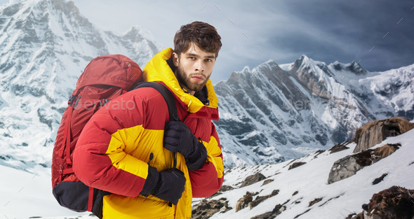 Mountaineer in winter clothes with hiking equipment against snowy landscape - Stock Photo - Images