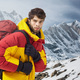 Mountaineer in winter clothes with hiking equipment against snowy landscape - PhotoDune Item for Sale