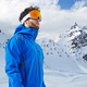 The mountaineer in winter clothes and ski ultraviolet protected mask against a snowy mountain - PhotoDune Item for Sale