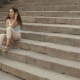 Attractive Brunette Girl Listens Music and Sitting on the Stairs Outside - VideoHive Item for Sale