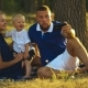 Happy Family Is Sitting on the Grass and Doing Selfie with a Baby at Sunset in the Park. Father and - VideoHive Item for Sale
