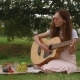 Slide Shot of Beautiful Girl Playing Acoustic Guitar in Park. - VideoHive Item for Sale