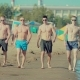 Sports and Young Guys Walking Along the Sandy Beach - VideoHive Item for Sale