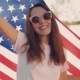 Portrait of Beautiful Young Woman in Sunglasses Holding American Flag While Smiling Proudly in the - VideoHive Item for Sale