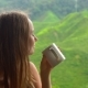 Shot of a Young Woman Sitting in a Cafe with a View on Highlands Tea Terraces and Drinking Tea - VideoHive Item for Sale