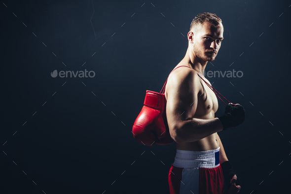 Fighter standing with gloves hanging over his back. - Stock Photo - Images