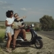 Friends Discussing New Location on a Highway with a Bike and Green Sunny Landscape in the Back - VideoHive Item for Sale