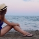 Pretty Young Female in Panama Sits on Sand Beach on the Shore in the Sunset - VideoHive Item for Sale