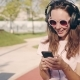 Smiling and Laughing Young Woman or Teenage Girl with Smartphone and Headphones Listening To Music - VideoHive Item for Sale