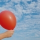 Air Comes From the Red Air Balloon and It Becomes Limp. Against the Background of the Blue Sky - VideoHive Item for Sale