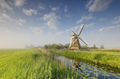 windmill on green meadow by river - PhotoDune Item for Sale
