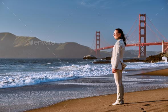 Woman on beach near Golden Gate Bridge - Stock Photo - Images
