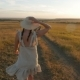Girl in the Hat and Dress Is on the Field at Sunset - VideoHive Item for Sale