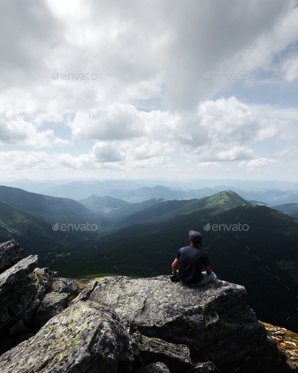 A lone tourist sitting on the edge of the cliff - Stock Photo - Images