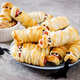 Scary sausage mummies in dough with funny eyes on table. Funny decoration. Halloween food. - PhotoDune Item for Sale