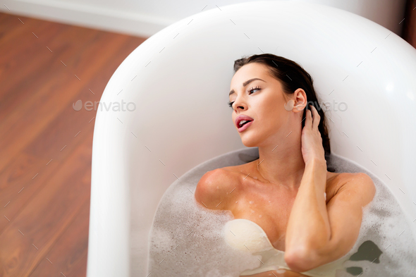 c8def56117 Beautiful young woman enjoying time in bathtub - Stock Photo - Images