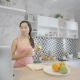 Beautiful Asian Woman Eating Apple While Checking Networks on Her Laptop in the Kitchen - VideoHive Item for Sale