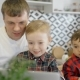 Father and Two Sons Watching Cartoons on the Laptop in the Kitchen. - VideoHive Item for Sale