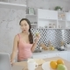 Attractive Young Woman Is Using Laptop, Eating Apple in Modern Kitchen - VideoHive Item for Sale