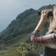 A Blond Woman with Binoculars on Top of a Mountain Enjoys a Surrounding - VideoHive Item for Sale