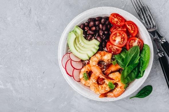 Spicy Shrimp Burrito Buddha Bowl with wild rice, spinach, radish,  tomatoes, black beans and avocado - Stock Photo - Images