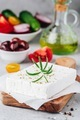 Homemade greek cheese feta with rosemary on wooden cutting board. Ingredients for greek salad - PhotoDune Item for Sale