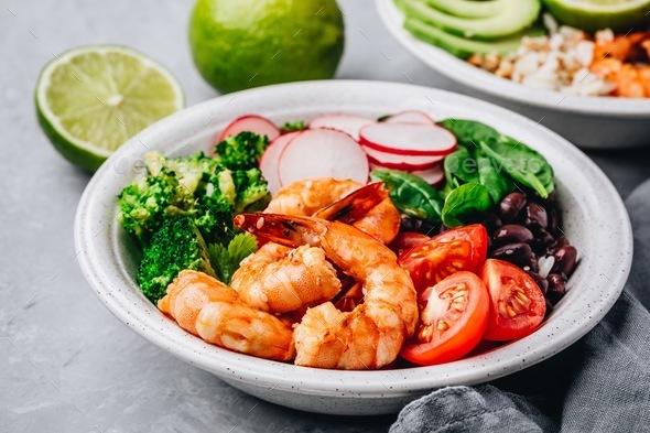 Spicy Shrimp Burrito Buddha Bowl with wild rice, spinach, radish,  tomatoes, black beans - Stock Photo - Images